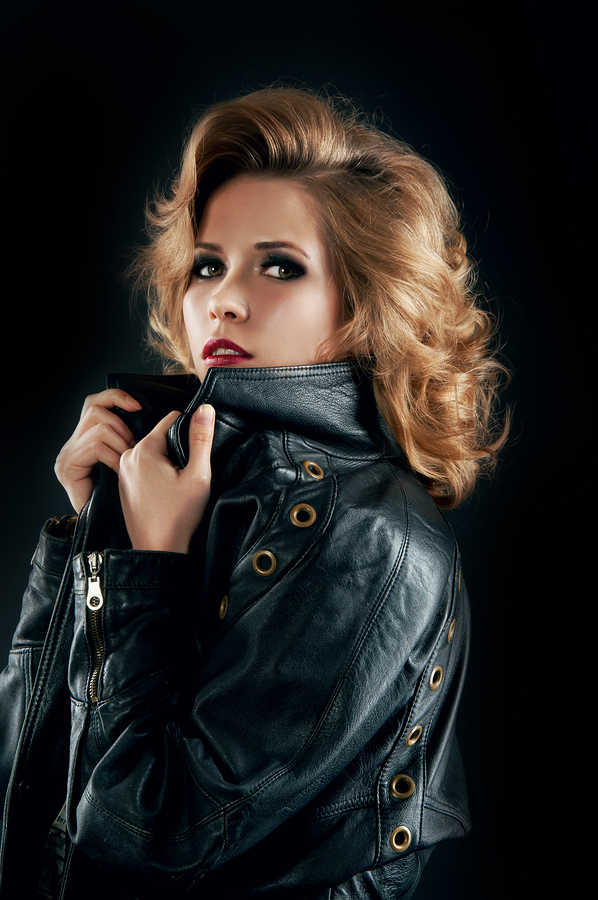 Studio Portrait Of Blonde Woman In Leather Biker Jacket.