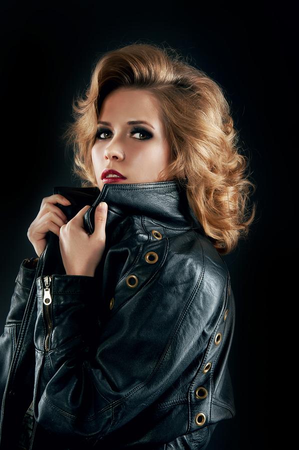 Studio Portrait Of Blonde Woman In Leather Biker Jacket.
